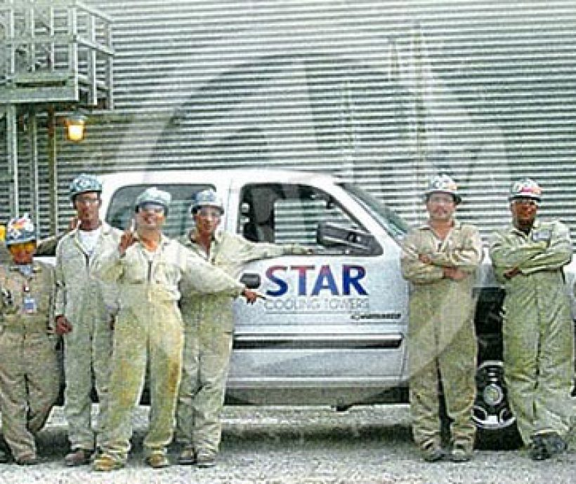 STAR Cooling Towers employees standing in front of truck wearing overalls and safety helmets